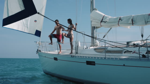 Young adult couple jumping in sea from sail boat