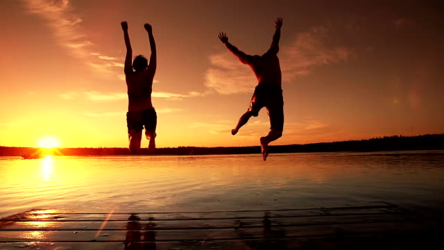 young adult couple jumps into lake. - sunset stock videos & royalty-free footage