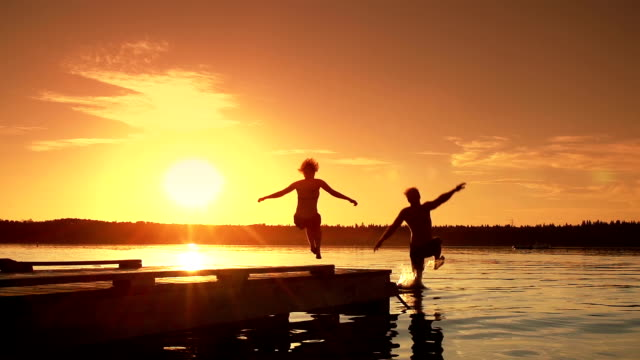 young adult couple jumps into lake. - jumping stock videos & royalty-free footage