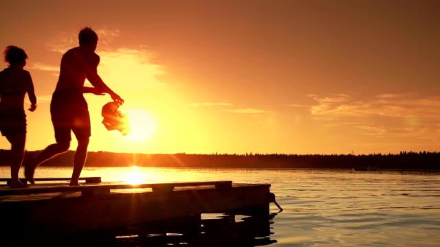vídeos de stock, filmes e b-roll de jovem adulto casal saltos para o lago. - imaginação
