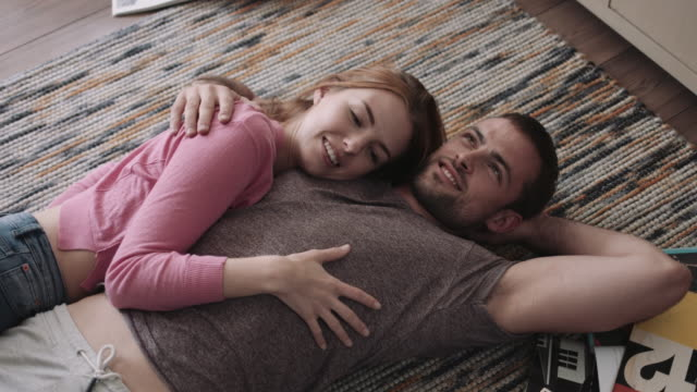 Young adult couple laying down on carpet in new home