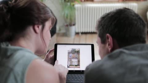 vidéos et rushes de young adult couple looking online at real estate on digital tablet - vue de dos
