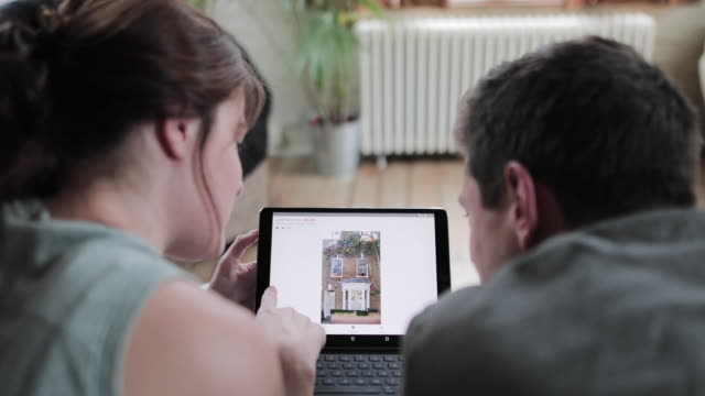 young adult couple looking online at real estate on digital tablet - searching stock videos & royalty-free footage