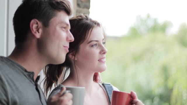 vídeos y material grabado en eventos de stock de young adult couple looking out of window in new home - mirar por la ventana