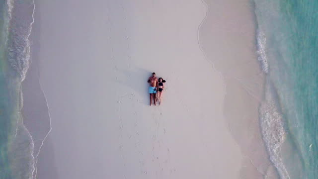 vídeos de stock e filmes b-roll de young adult couple lying together on a sandbank against turquoise water in maldives - lua de mel