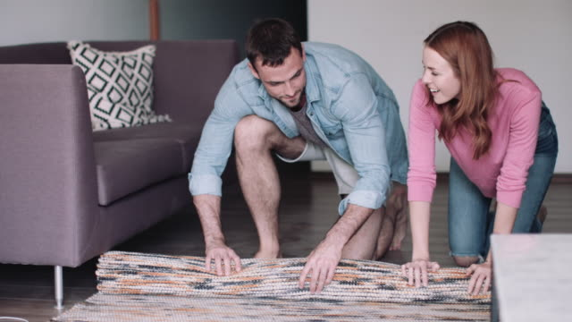 vidéos et rushes de young adult couple moving furniture in new home - tapis