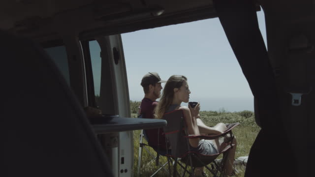 young adult couple on road trip talking and drinking coffee outside campervan and looking at view over sea - weekend activities stock videos & royalty-free footage
