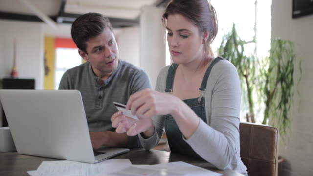 young adult couple online banking together - papierkram stock-videos und b-roll-filmmaterial
