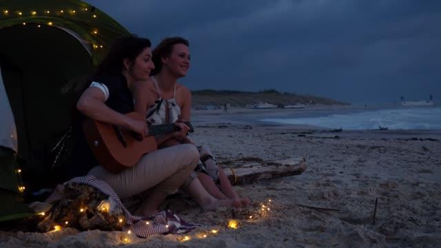 giovane coppia di adulti che suona la chitarra al tramonto in una tenda sulla spiaggia - chitarra video stock e b–roll