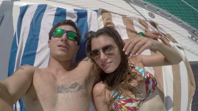 vídeos de stock, filmes e b-roll de young adult couple romantic on deck of sail boat taking selfie - toalha de praia