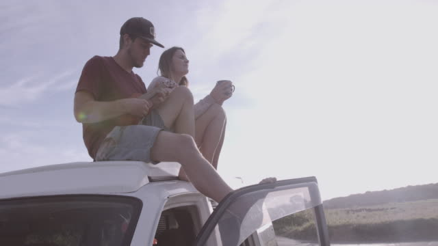 vídeos y material grabado en eventos de stock de young adult couple sitting on roof camper van enjoying view and playing music - trailer