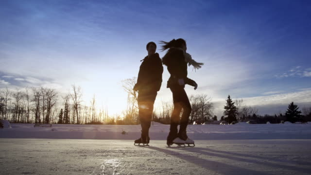 young adult couple skating together on ice. - ice skating stock videos & royalty-free footage
