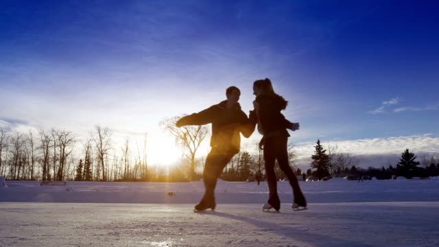 Young adult couple skating together.