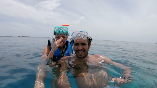young adult couple taking a selfie with scuba mask in the sea - symbols of peace stock videos & royalty-free footage