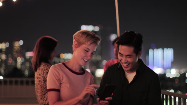 young adult couple taking selfie with city skyline at night - 韓国人点の映像素材/bロール
