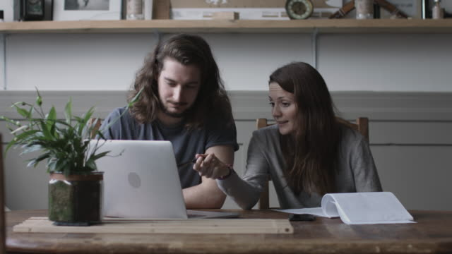 vidéos et rushes de young adult couple using a working on finance application together - budget