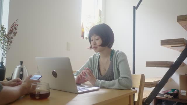 自宅でラップトップを使用して若い大人のカップル - 職探し点の映像素材/bロール