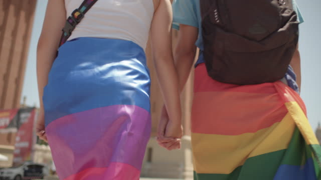 vídeos y material grabado en eventos de stock de young adult couple walking holding hands. dressing rainbow flag. going to barcelona gay pride parade - orgullo