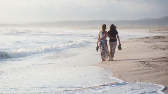 ビーチで一緒に歩いて若い大人のカップル - パレオ点の映像素材/bロール