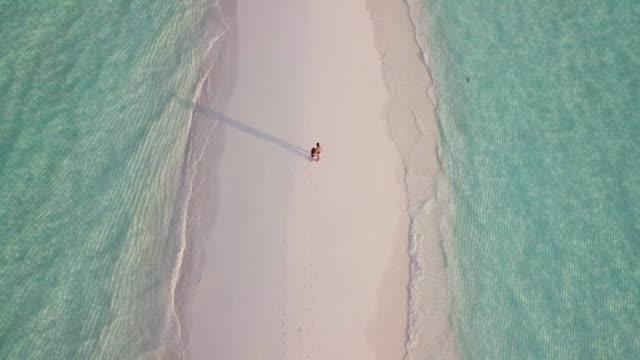 junges erwachsenes paar zu fuß zusammen auf einer sandbank gegen türkisfarbenes wasser auf den malediven - malediven stock-videos und b-roll-filmmaterial