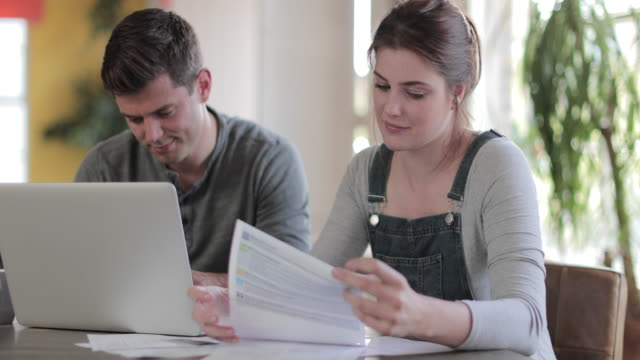 vídeos de stock, filmes e b-roll de young adult couple working on finance application together - pagando
