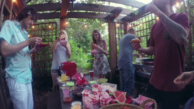 young adult  eating food pool party outdoor summer bbq - villa stock videos & royalty-free footage