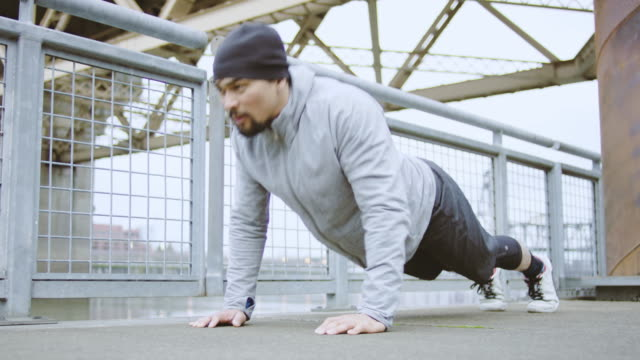 Young adult ethnic male doing pushups outdoors in an urban city setting