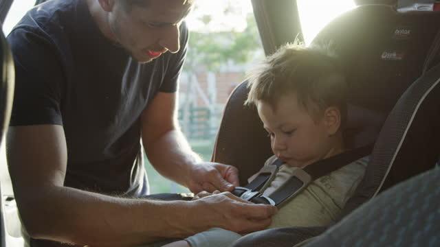 vídeos de stock e filmes b-roll de young adult father fastening his son´s seat bealt - segurança
