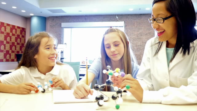 young adult female asian teacher teaches elementary and junior high student about a molecular structure in science class - junior high student stock videos and b-roll footage