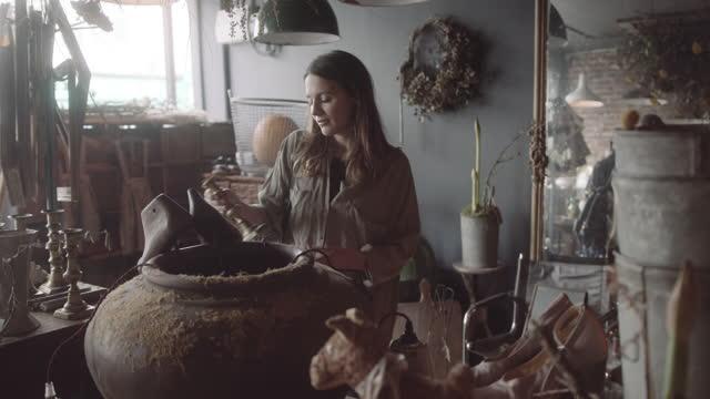 vidéos et rushes de young adult female browsing store for home decoration - antiquités