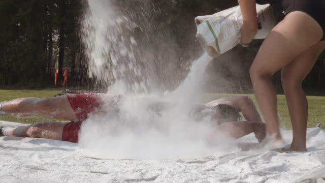 uhd 4k: young adult female competing in a fun mud run race - superwoman stock videos and b-roll footage
