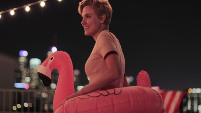 young adult female dancing in a pool inflatable at a rooftop party - dressing up stock videos & royalty-free footage