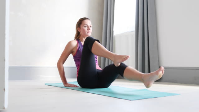 young adult female doing yoga at home - inarcare la schiena video stock e b–roll