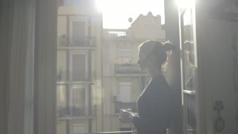 young adult female enjoying sunshine and drink on balcony - window bildbanksvideor och videomaterial från bakom kulisserna