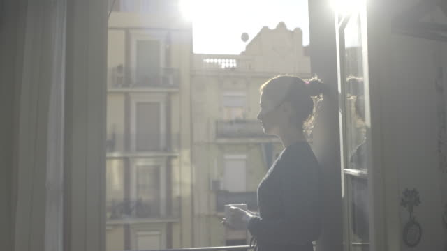 vidéos et rushes de young adult female enjoying sunshine and drink on balcony - regarder par la fenêtre