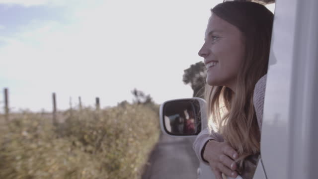 young adult female hanging out of window of camper van on road trip at sunset - land vehicle stock videos & royalty-free footage