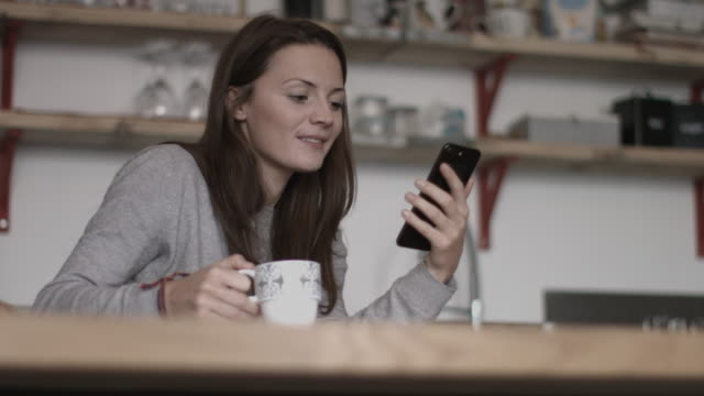 young adult female having morning coffee and checking smartphone - brown hair stock videos & royalty-free footage