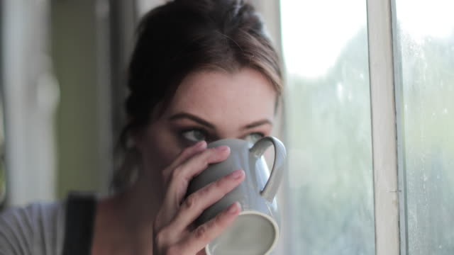 young adult female having morning coffee looking out of window - freckle stock videos & royalty-free footage