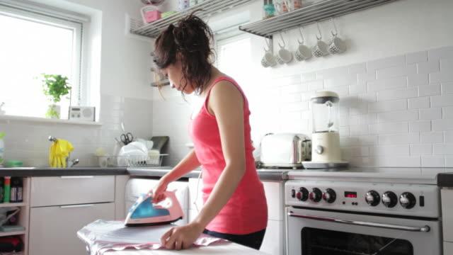 若い大人女性の衣類のアイロンサービスのキッチン - アイロン点の映像素材/bロール