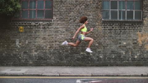young adult female leaping in the air with brick wall backdrop - hopp bildbanksvideor och videomaterial från bakom kulisserna