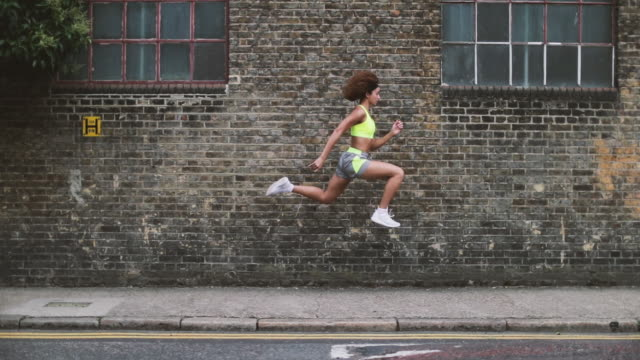 vídeos y material grabado en eventos de stock de young adult female leaping in the air with brick wall backdrop - pared