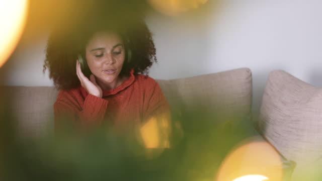 vídeos y material grabado en eventos de stock de young adult female listening to christmas songs - auriculares aparato de información