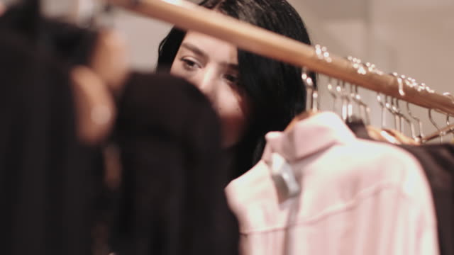 Young adult female looking at clothes in shop