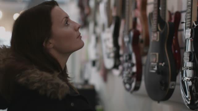 young adult female looking at guitar in shop - ミュージックショップ点の映像素材/bロール