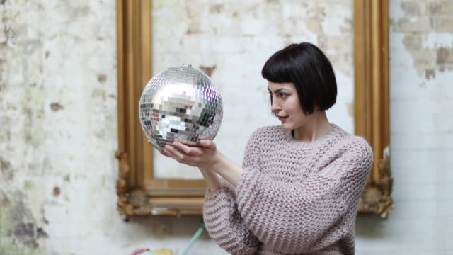 Young adult female looking at her reflection in disco ball