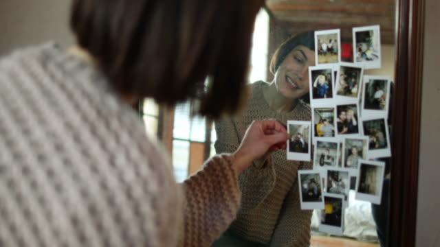 vidéos et rushes de young adult female looking at photos of friends - souvenirs