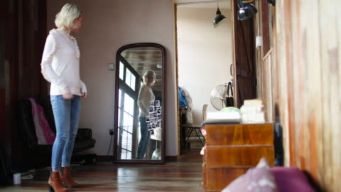 young adult female looking at reflection in mirror - jeans stock videos & royalty-free footage