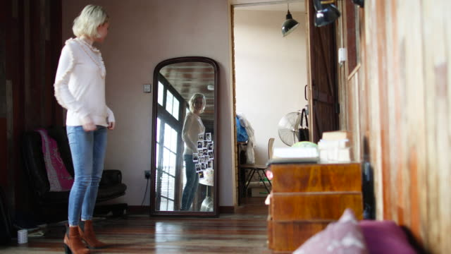 young adult female looking at reflection in mirror - trousers stock videos & royalty-free footage