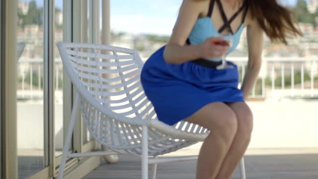 stockvideo's en b-roll-footage met young adult female on balcony in blue summer dress drinking wine - balkon