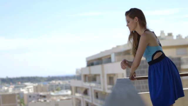 young adult female on balcony in blue summer dress - balkon stock-videos und b-roll-filmmaterial